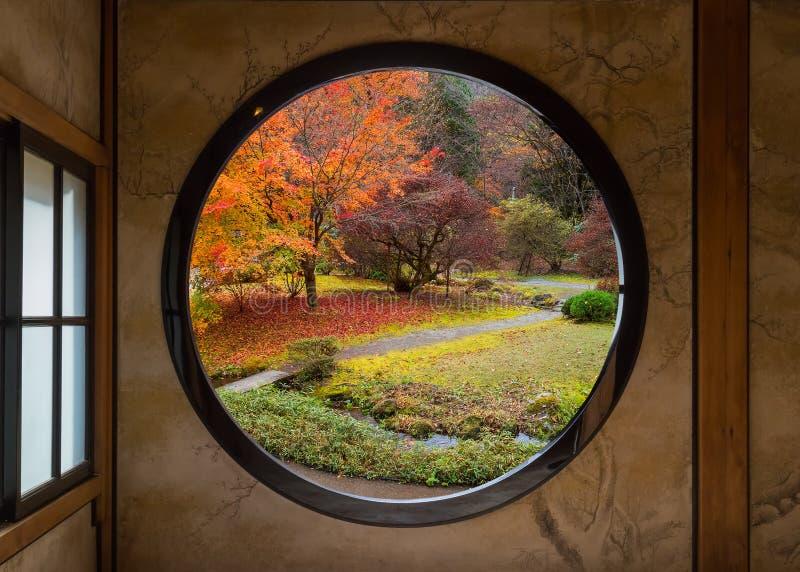 Jardín a través de una ventana redonda imagen de archivo