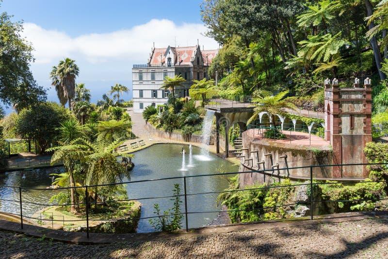 Jardín tropical con la charca y el palacio en Funchal, isla de Madeira fotografía de archivo