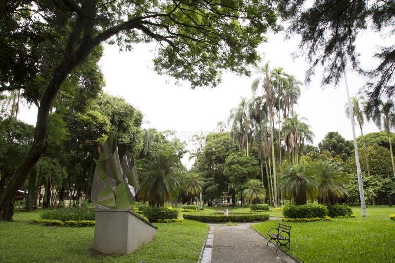 Jardín tropical hermoso con el banco y la escultura fotos de archivo