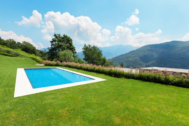 Jardín verde con la piscina foto de archivo libre de regalías