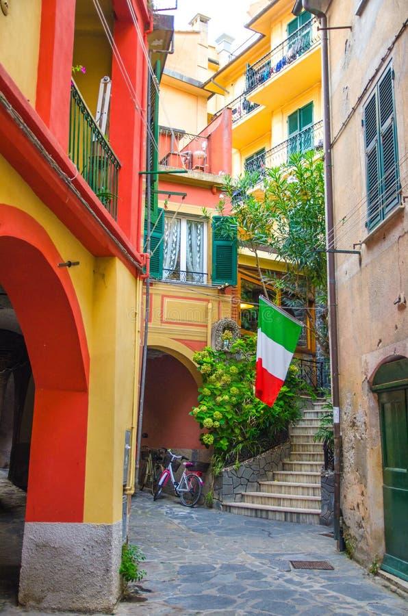 Jarda italiana pequena típica com casas das construções, escadas, janela do obturador e a bandeira italiana na vila de Monterosso fotografia de stock royalty free
