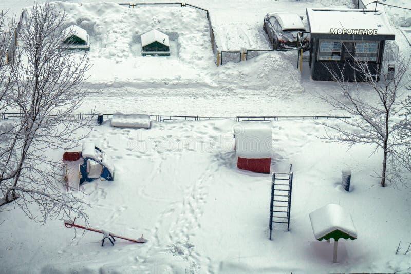 Jarda usual de Moscou com campo de jogos das crianças e quiosque da troca do gelado no inverno nevado Vista de acima imagens de stock