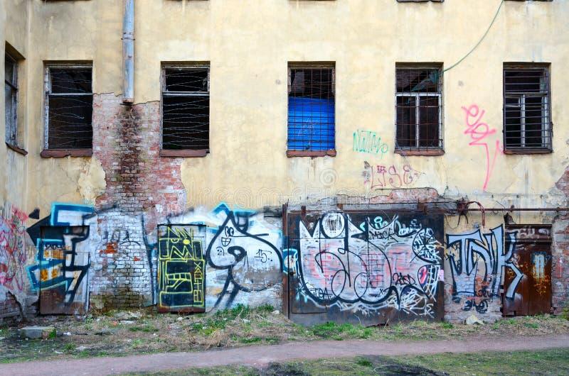 Jardas de St Petersburg velho Grafittis na parede da construção abandonada na pista de Bolshoy Kazachiy no centro histórico da ci imagens de stock