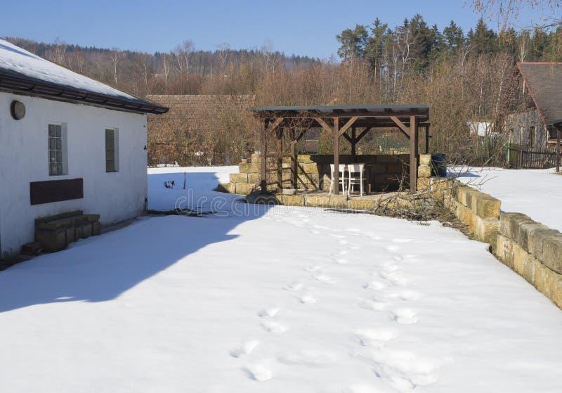 Jardim coberto de neve no dia ensolarado do inverno com a casa branca velha, cottagge de madeira, parede do arenito e a alcova de fotografia de stock