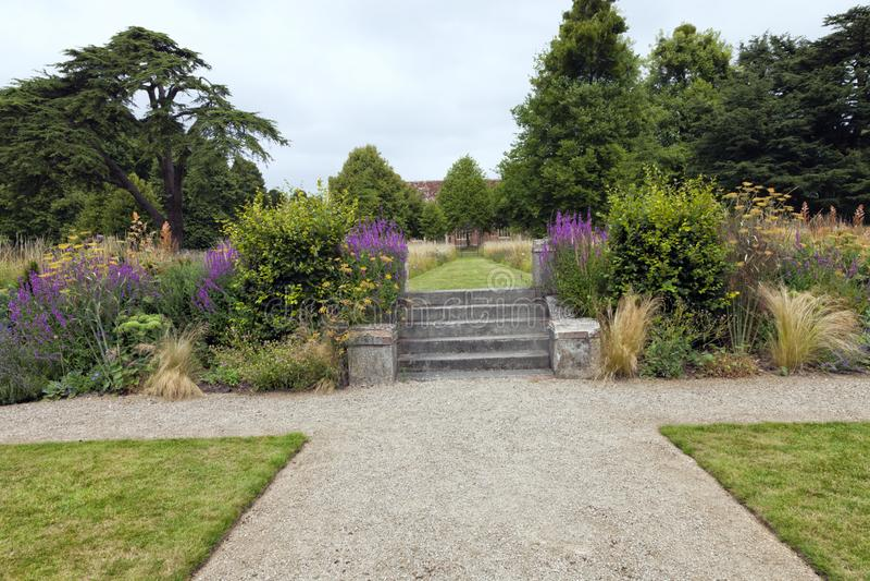 Jardim com as plantas da flor selvagem, as escadas de pedra e o trajeto do cascalho fotografia de stock