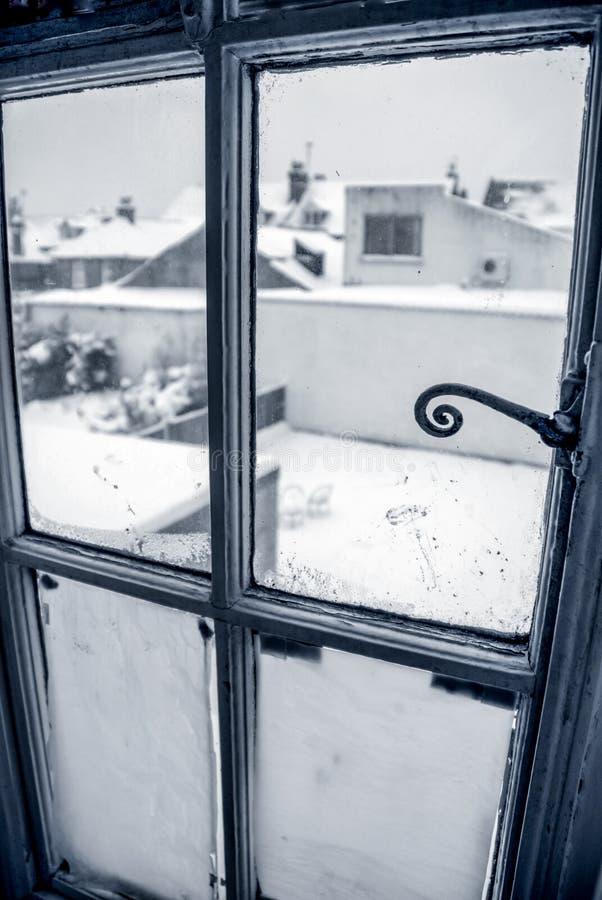 Jardim do coverd da neve visto completamente uma janela fotografia de stock