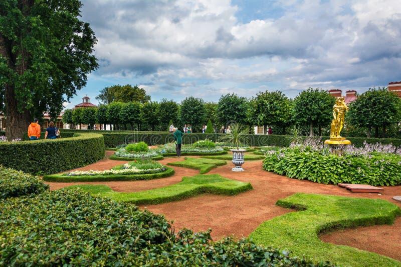Jardim do palácio de Monplaisir O guarda de serviço fêmea varre o lixo foto de stock royalty free