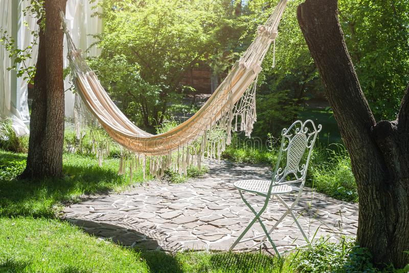 Jardim do verão com a rede de suspensão para o abrandamento Tempo preguiçoso, sesta Paisagem bonita, dia ensolarado imagem de stock