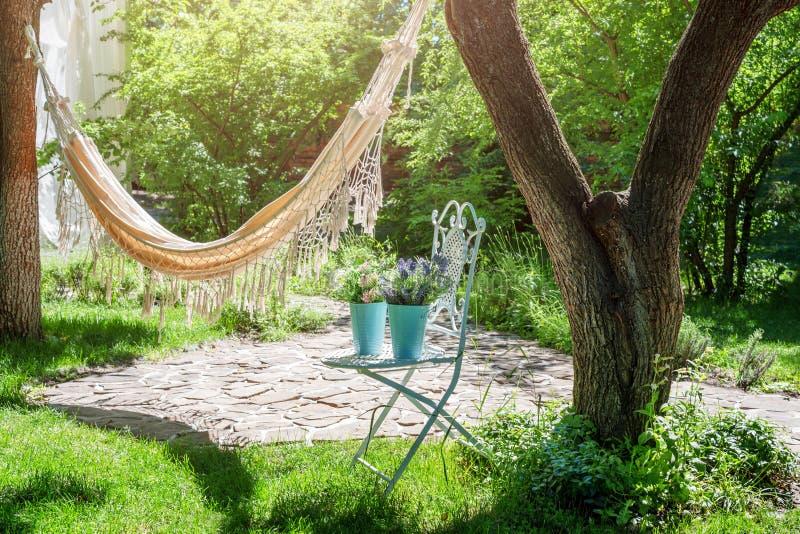 Jardim do verão com a rede de suspensão para o abrandamento Tempo preguiçoso, sesta Paisagem bonita, dia ensolarado imagem de stock royalty free