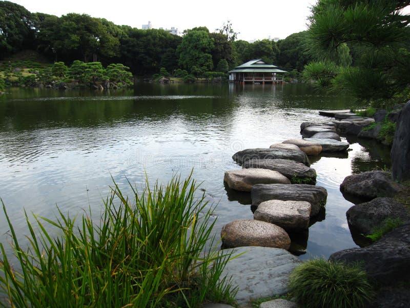 Jardim japonês tradicional com lagoa e alpondras imagem de stock royalty free