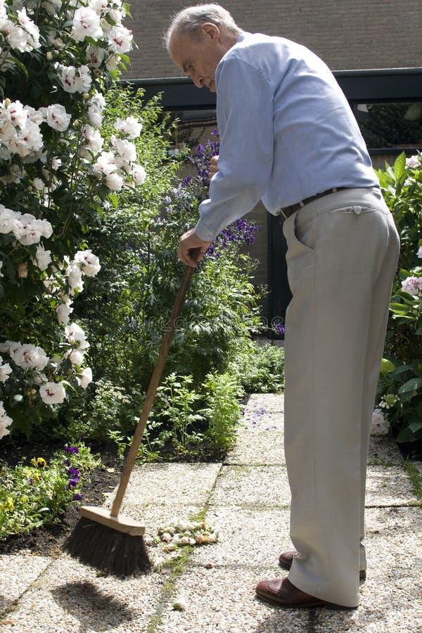 Jardim sênior da limpeza do macho 80+ com vassoura fotografia de stock royalty free
