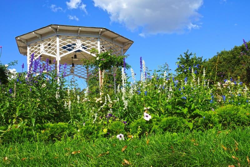 Jardim verde com flores e um miradouro branco fotografia de stock