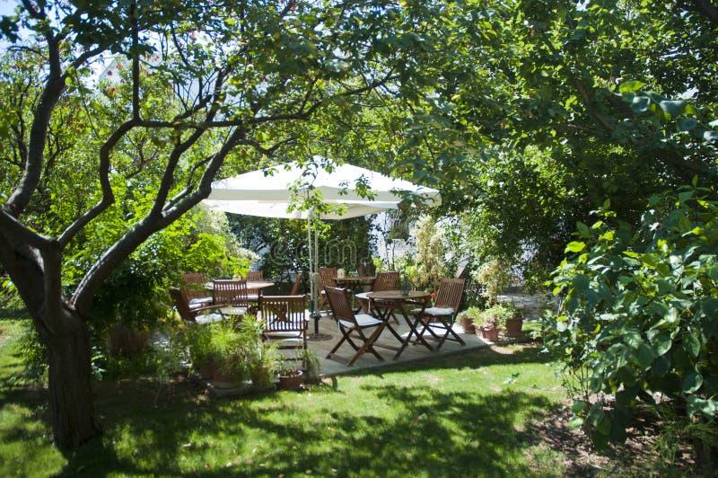 Jardim verde de assento de madeira no hotel pequeno, bodrum do lugar fotografia de stock