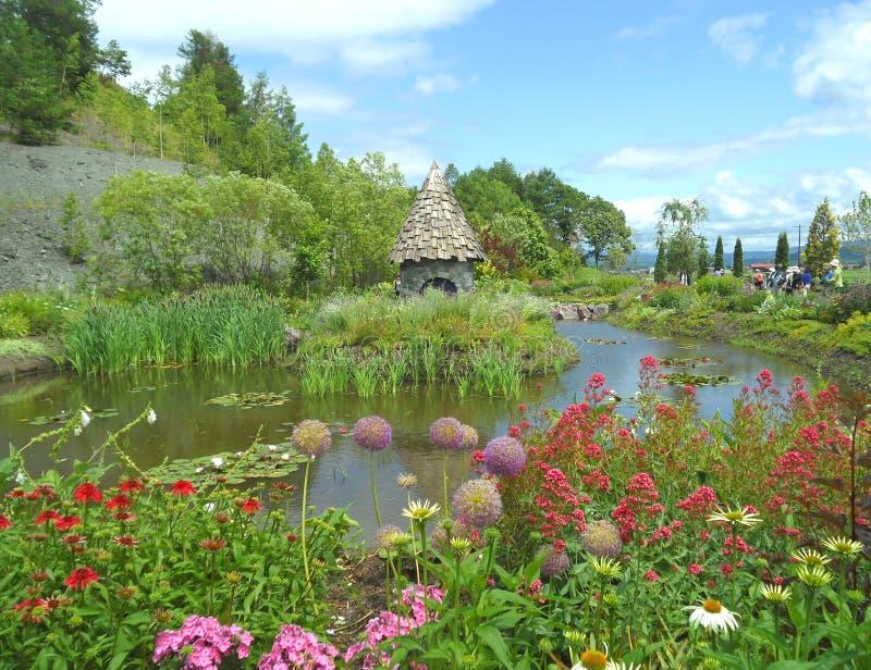 Jardin anglais de style campagnard avec un cottage féerique sur l'étang photographie stock