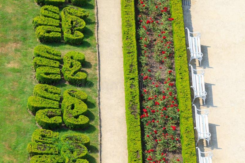 Jardin anglais ornemental avec les bancs blancs photo libre de droits