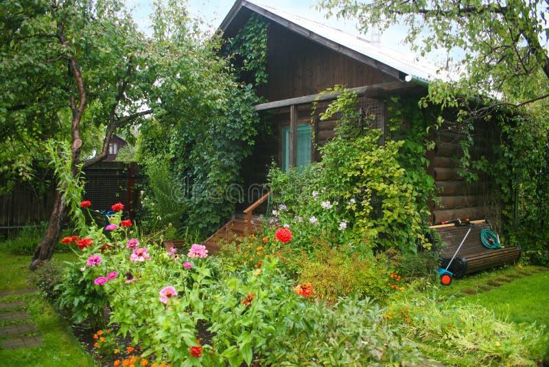 Jardin avec la maison en bois photo stock