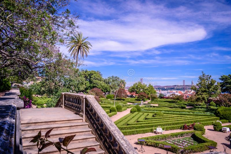 Jardin botanique d'Ajuda, plusieurs arbres et escalier, comme fond 25ème d'April Bridge au-dessus du Tejo et du Christ le roi, Li images stock