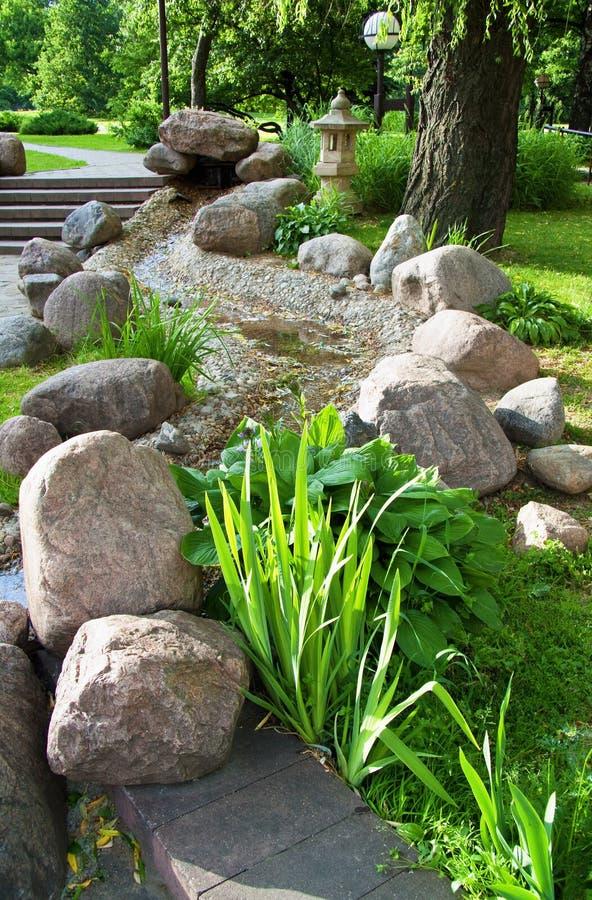 Jardin d'été avec des centrales et des pierres photo stock