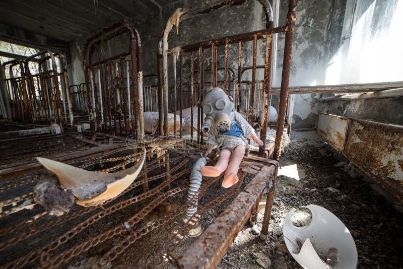 Jardin d'enfants abandonn? dans la zone d'exclusion de Chernobyl Jouets perdus, une poup?e cass?e L'atmosph?re de la crainte et d image stock