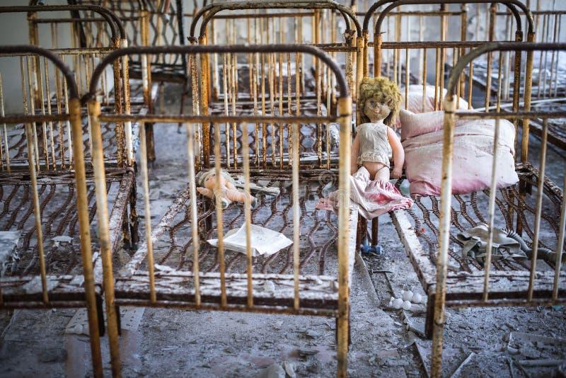 Jardin d'enfants abandonn? dans la zone d'exclusion de Chernobyl Jouets perdus, une poup?e cass?e L'atmosph?re de la crainte et d photo stock