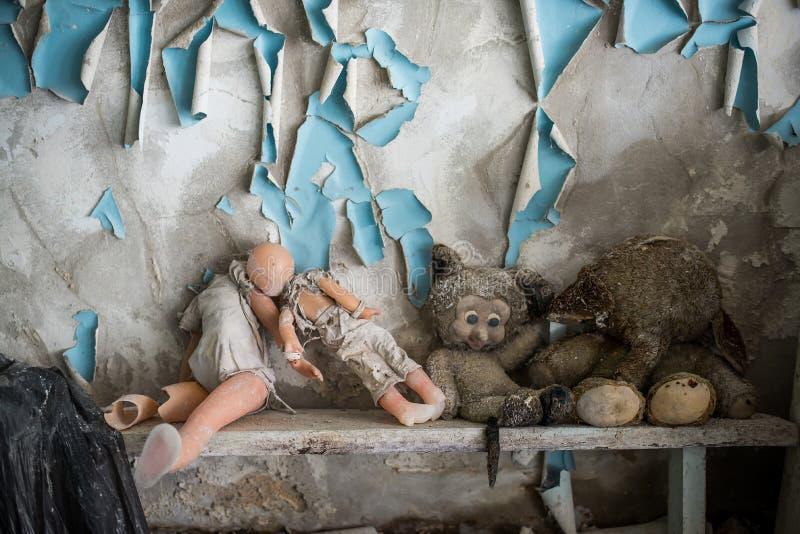 Jardin d'enfants abandonn? dans la zone d'exclusion de Chernobyl Jouets perdus, une poup?e cass?e L'atmosph?re de la crainte et d images libres de droits