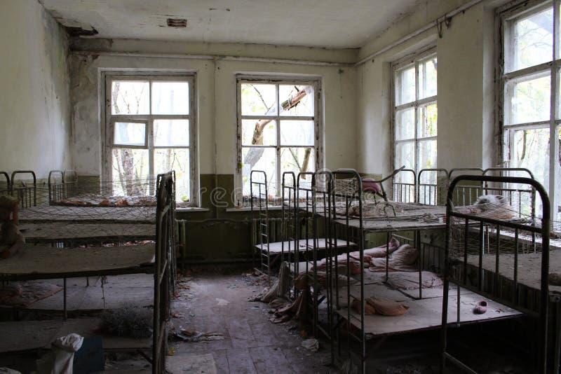 Jardin d'enfants abandonn? dans la zone d'exclusion de Chernobyl Jouets perdus, une poup?e cass?e L'atmosph?re de la crainte et d photos libres de droits