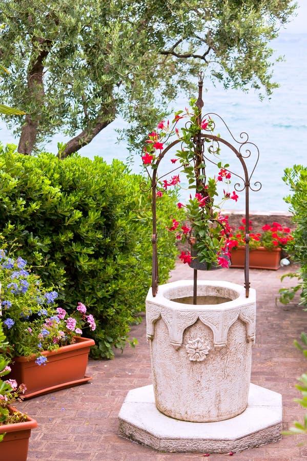 Jardin de fleur avec le puits de pierre image libre de droits