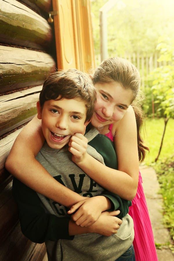 Jardin de l'adolescence de sourire d'étreinte de fille de garçon d'enfants de mêmes parents photo libre de droits