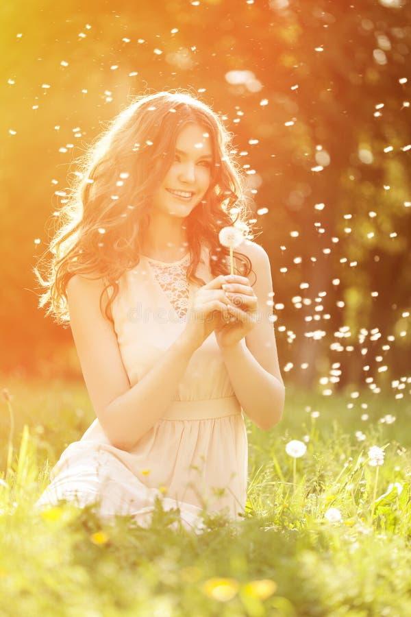 Jardin de soufflement de pissenlit de jeune de ressort femme de mode au printemps S images stock