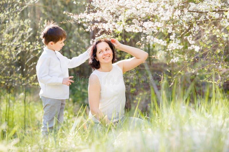 Jardin heureux de femme et d'enfant au printemps photo stock