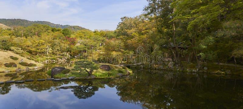 Jardin japonais avec un petit lac, un cottage caché parmi des arbres d'érable japonais et des pins photo stock