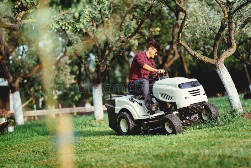 Jardinando com o trabalhador que usa um passeio no trator, segadeira para cortar a grama imagem de stock royalty free