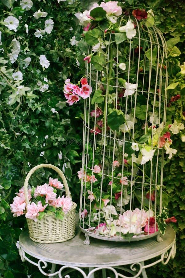 Jardine com conversão verde a tabela e a cesta de vime forjadas nela foto de stock royalty free
