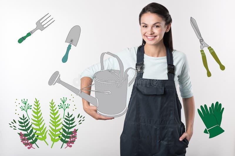 Jardineiro alegre que guarda uma lata molhando e que olha contente fotografia de stock royalty free