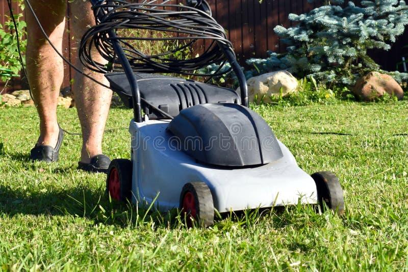 Jardineiro com a eletricista-segadeira Cortador de grama de trabalho com grama no jardim fotografia de stock
