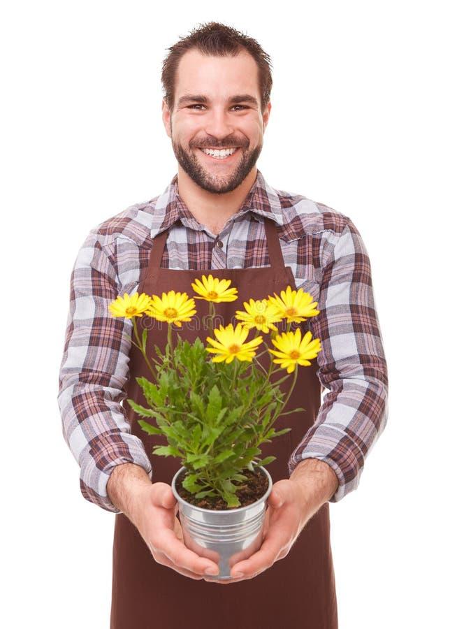 Jardineiro de sorriso que guarda flores imagem de stock