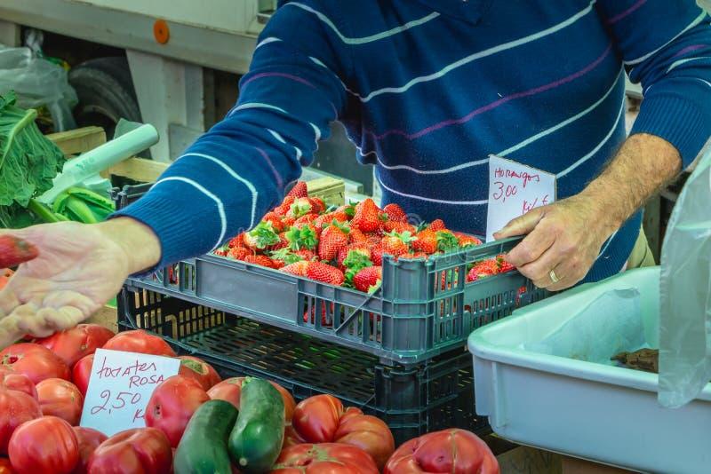 Jardineiro do mercado que propõe morangos em um mercado municipal fotos de stock