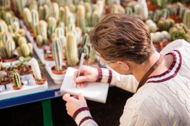 Jardineiro masculino que faz anotações sobre a condição dos cactos imagens de stock