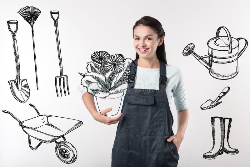 Jardinero alegre que sostiene una planta grande y que parece feliz foto de archivo