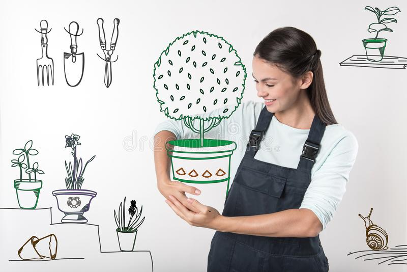 Jardinero bueno que sonríe mientras que sostiene una maceta grande fotos de archivo