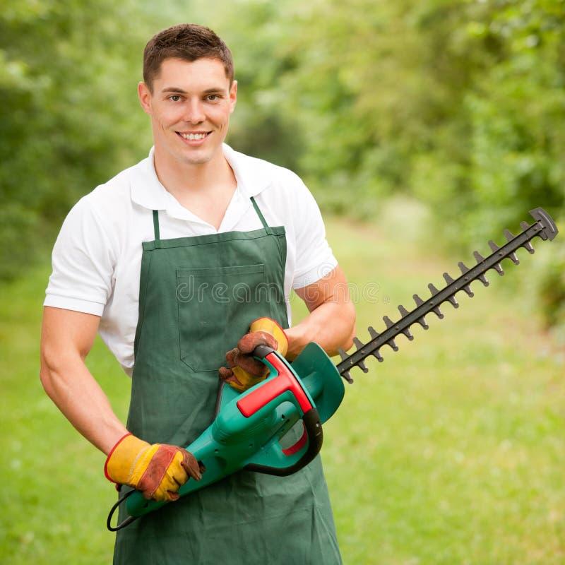 Jardinero con el condensador de ajuste de seto fotografía de archivo