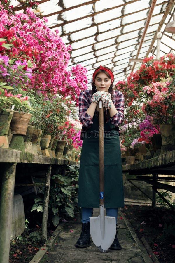 Jardinero de la muchacha en delantal y guantes con una pala grande en el invernadero, mirando la cámara foto de archivo