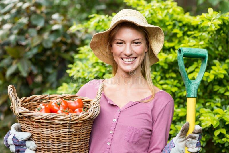 Jardinero de sexo femenino que sostiene la cesta del tomate y la herramienta del trabajo fotografía de archivo libre de regalías