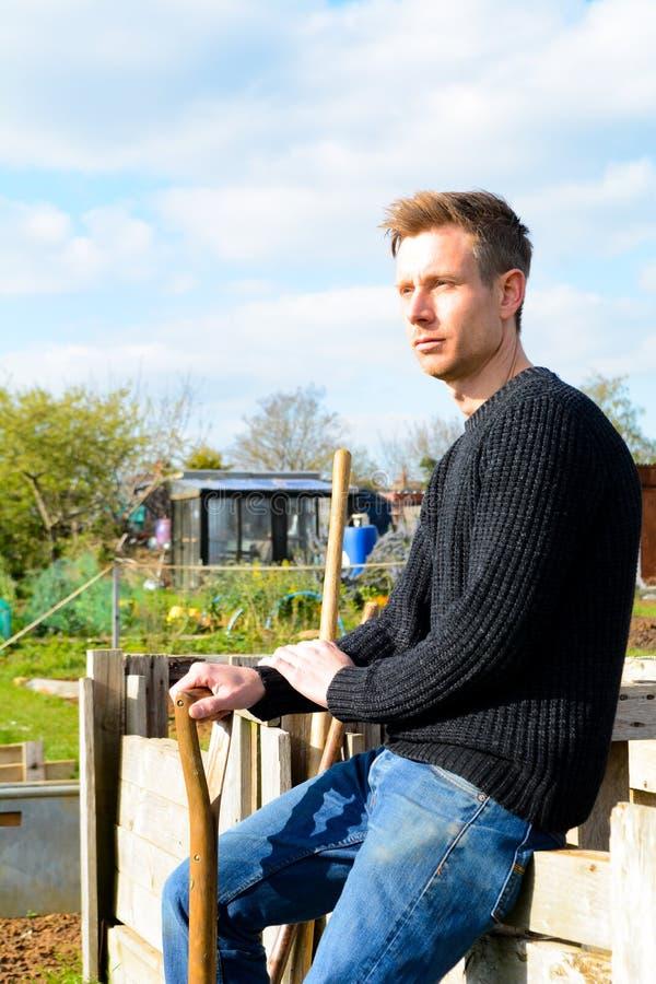 Jardinero de sexo masculino en el jardín de la comunidad con las herramientas del trabajo imagen de archivo libre de regalías