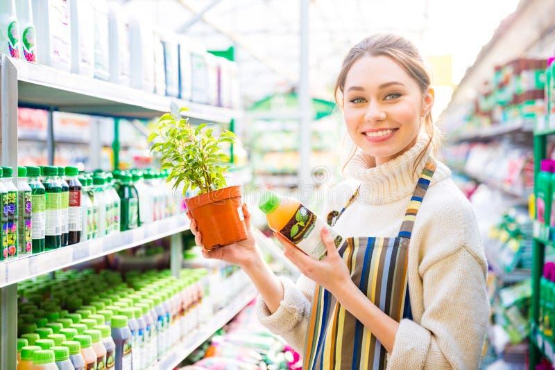 Jardinero feliz de la mujer que compra sustancias químicas agrícolas para las plantas foto de archivo