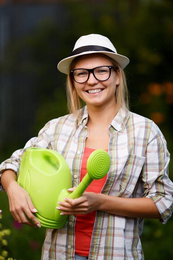 Jardinero hermoso de la mujer joven que sostiene la regadera verde foto de archivo libre de regalías