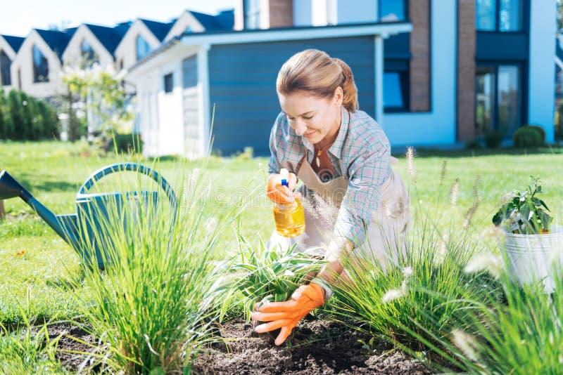Jardinero hermoso que cuida que asperja un poco de agua en sus plantas preferidas fotografía de archivo