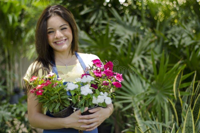 Jardinero lindo que lleva algunas flores foto de archivo libre de regalías
