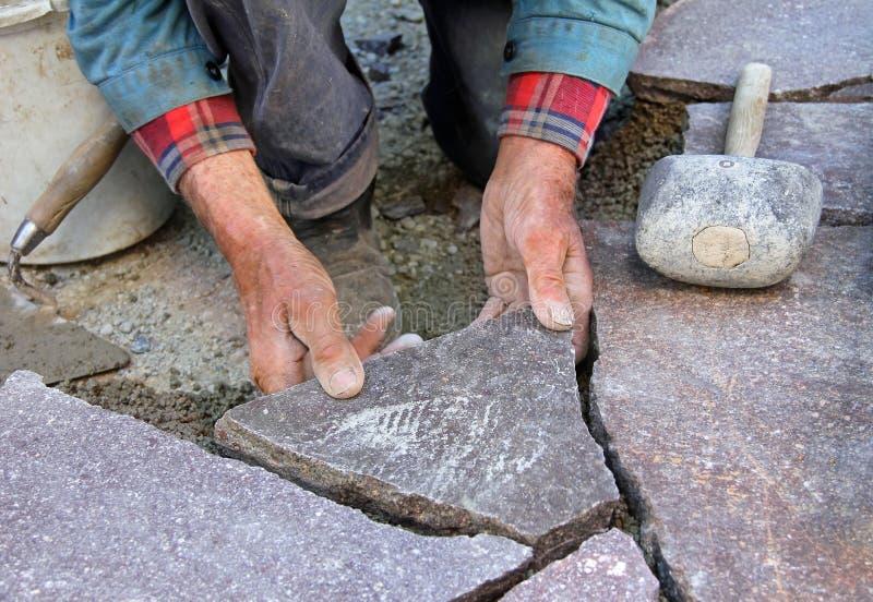 Jardinero mayor que pavimenta la terraza de piedra natural, preci profesional foto de archivo