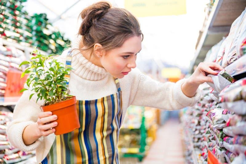 Jardinero pensativo de la mujer en compras en tienda del jardín imagen de archivo libre de regalías